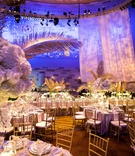 wedding reception gold chairs white orchid rose hydrangea centerpiece gold palm leaves purple light