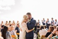 Groom in navy blue suit kisses bride in middle of aisle