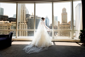 Bride looking out floor to ceiling windows in Chicago bridal suite a line gown and veil cathedral