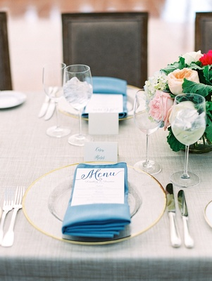 Wedding reception gold clear charger plate rim with blue napkin menu with blue calligraphy escort