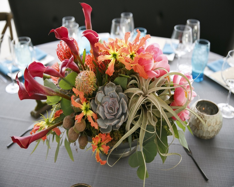 Multicolored centerpiece perfectly complementing the blue napkins on this table.