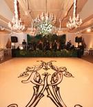 dance floor with large, ornate monogram in black, chandeliers above