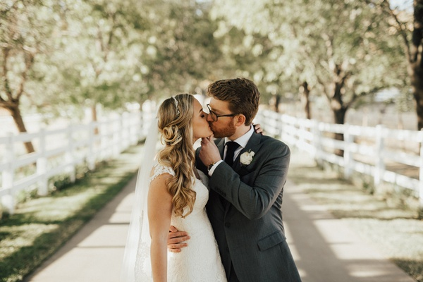 groom holds bride by the chin and around her waist while kissing her as they stand on a path