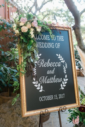 chalkboard wedding welcome sign with flowers and greenery