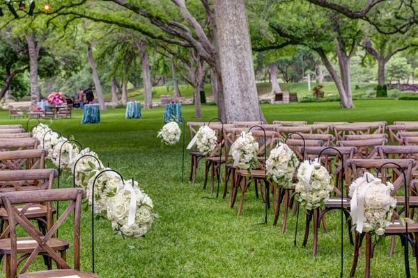 Outdoor wedding ceremony with white rose and hydrangea aisle markers