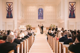 wedding ceremony at traditional church with stained glass window guests in pews christian ceremony