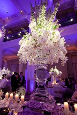 Ice sculpture vase with white orchid flower arrangement
