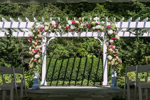 wedding ceremony arbor outdoor venue pink white orange flowers greenery