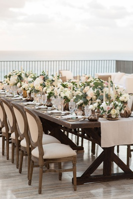 wedding reception on rooftop outdoors cabo mexico wood table round back french chair low centerpiece