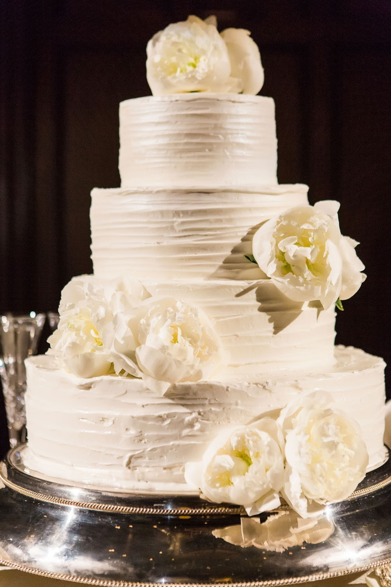Four layer buttercream frosting wedding cake with fresh flowers peony blooms on top and tier lemon
