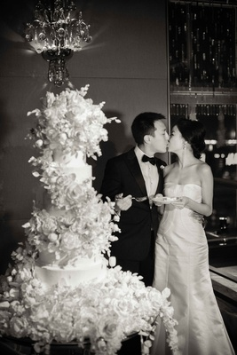 Black and white photo of bride in strapless wedding dress kissing groom after cake cutting