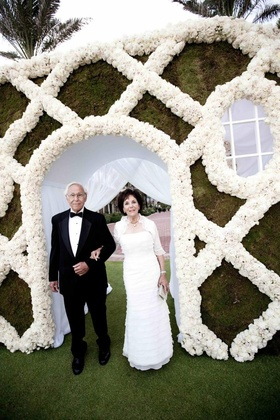 Father and mother of groom in front of flower wall