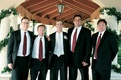 Groom in black tuxedo and tie and groomsmen in black tuxedos and red ties