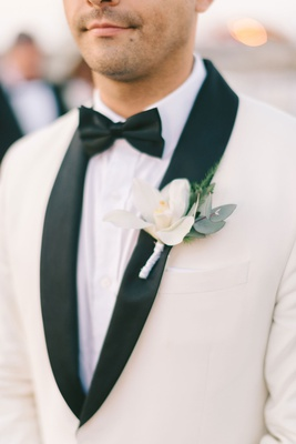 groom white white suit jacket black lapels boutonniere orchid variety green leaves black bow tie