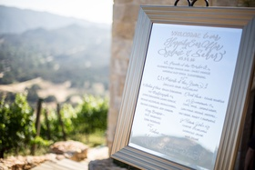 Mirror sign with welcome note and list of bridesmaids, groomsmen, ring bearers, flower girls, etc.