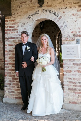 Bride in a strapless Hayley Paige dress with tiered skirt, veil, and father in black tuxedo