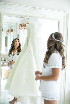 bride in short summer pajamas long hair headpiece crown looking in mirror at wedding dress vera wang