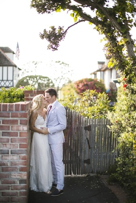 Couple kissing against bricks next to wood gate