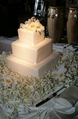 White wedding cake surrounded by orchids