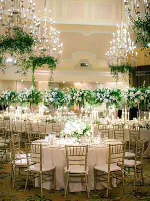 gold chiavari chairs, crystal chandeliers with greenery