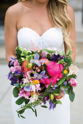 vibrant bridal bouquet with bright pink peonies, flowers in purple, peach, and yellow