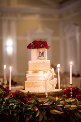 white cake red flowers purple monogram initial gold details candles ribbon renaissance wedding