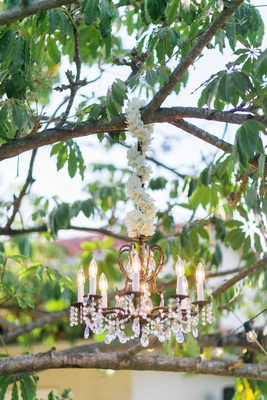 Chandelier hanging from tree at wedding reception with white flower garland wrapped around cord