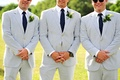 Groomsmen in blue seersucker suits, navy ties with dots, and calla lily boutonnieres