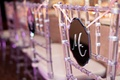 Die-cut mirror hanging from clear chair at reception