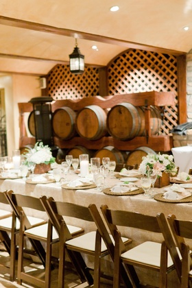 Oak wine barrels behind rustic elegant table