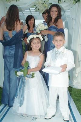 Little boy and girl wearing white on aisle runner