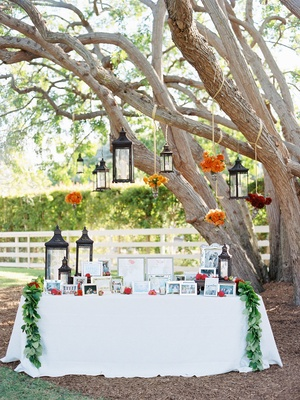White table under tree with Moroccan lanterns and flowers at photo table