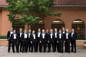 groom with groomsmen in tuxedos and one groomsman in uniform