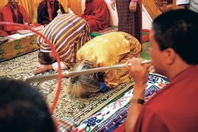 Bride and groom in child's pose during Buddhist wedding