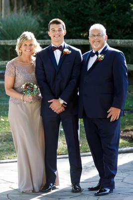 Groom in navy blue suit with burgundy bow tie with father of groom and mother in champagne taupe
