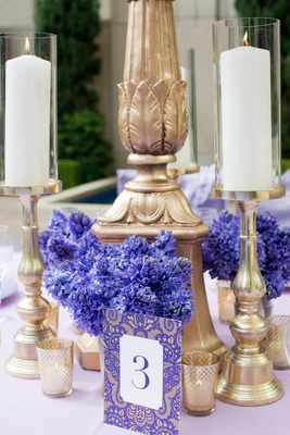 Wedding reception table with table number of purple and gold damask print, blue hyacinths