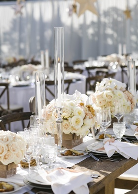 Wooden tables topped with short floral arrangements