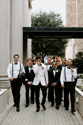 groom in white tuxedo jacket black bow tie groomsmen in suits and suspenders bow ties