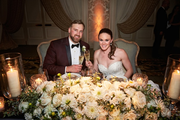 White flowers and greenery at sweetheart table chicago wedding maroon tuxedo for groom strapless