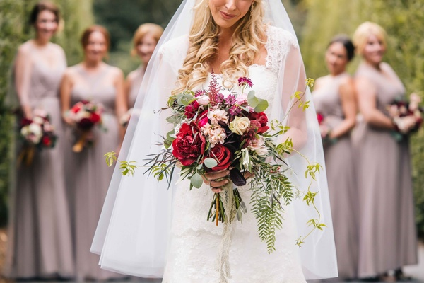 bride displays her autumn bouquet featuring wine colored florals with bridesmaids in background