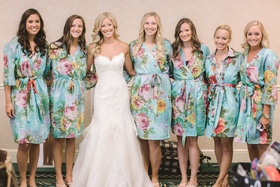 Bride in a strapless Hayley Paige dress with bridesmaids in blue robes with flowers