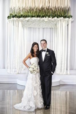 bride in oscar de la renta, groom in j. hilburn under chuppah of flowers and ribbons