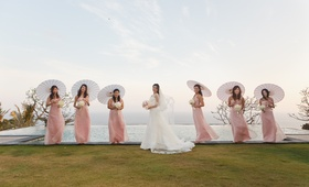 Bride with parasol bridesmaids in front of infinity pool