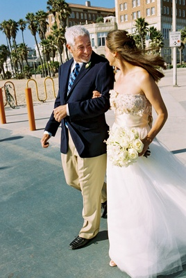Bride on father's arm in Santa Monica, California