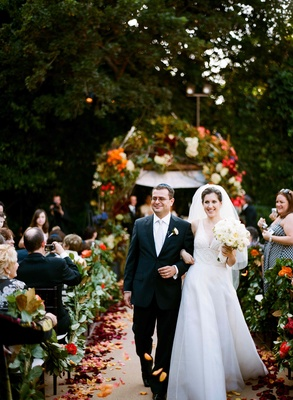 Bride and groom walk up garden ceremony aisle
