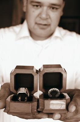 Sepia tone image of groom holding wedding ring boxes