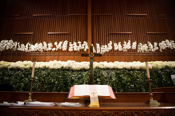 Orchid spray, hydrangea, English ivy, smilax decorating church altar at wedding