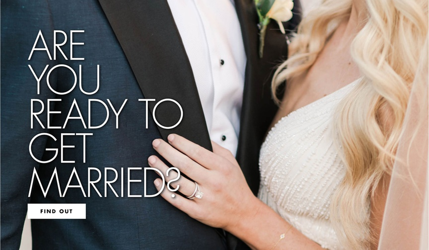 close-up of torsos with groom in navy tuxedo with black lapels and bride in beaded ivory dress