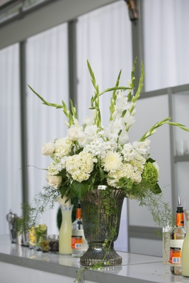Wedding reception bar decorated with urn and white flowers
