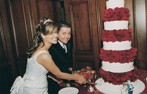 Bride and groom cut white cake with red roses